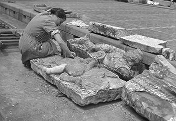Gezicht op mej. W.A.H. Crol die restanten van kunstwerken (beelden) onderzoekt op de binnenplaats van Museum Boymans, 1940. Bron Stadsarchief Rotterdam.