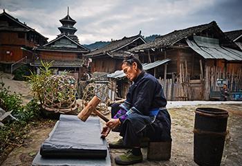 Een Dong vrouw kalandert een doek, die eerst met indigo is geverfd, Si Zhai, Liping Country. Foto Wu Zeng Ou