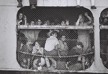 Joodse immigranten gekooid door de Britten op deExodus 1947, kijkend naar de haven van Haifa vóór hun deportatie. Foto: Hans Pinn, GPO